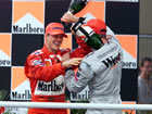 Michael Schumacher(Ferrari) and David Coulthard(McLaren) / Both happyon the podium with champagne